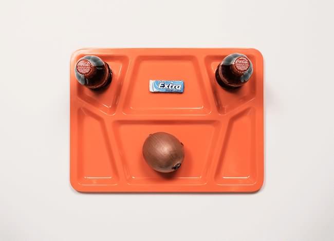 Vemos la bandeja de icopor color naranja con una ceboola de huevo y en la parte de arriba dos empacados con jugo