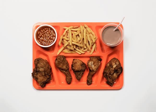 Vemos la bandeja color naranja  donde se la bandeja con fréjoles  papas fritas a la francesa y pollo y algo de chocolate