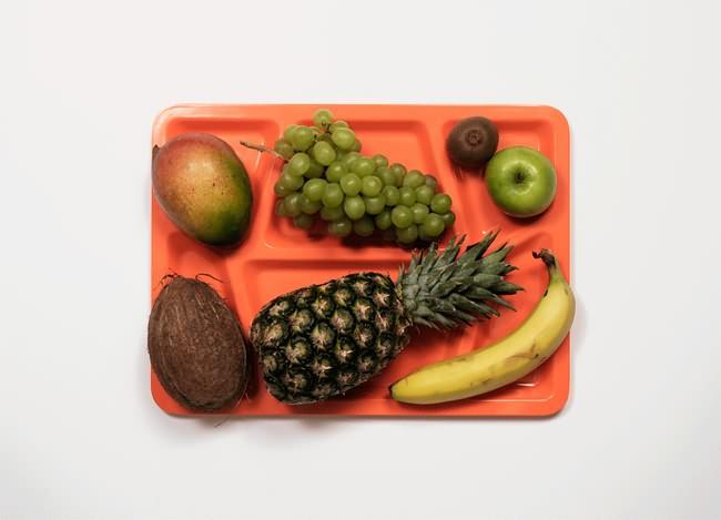 Vemos en una bandeja frutas de varias especies como naranjas piñas bananos