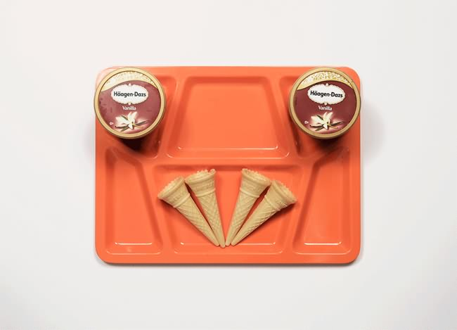 Vemos la bandeja naranja donde vemos dos cajas de  helado y cuatro conos o barquillos