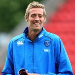 Vemos un jugador con chaqueta azul que muestra una inmensa sonrisa