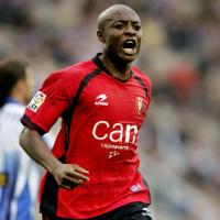Un  jugador de fútbol moreno con uniforme rojo  que corre y grita por la cancha