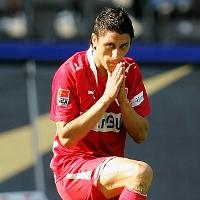 Vemos aun futbolista con uniforme rojo que se frota las manos y mira la camara