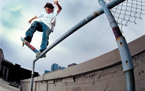 Un joven sobre una patineta la cual está equilibrando sobre una baranda