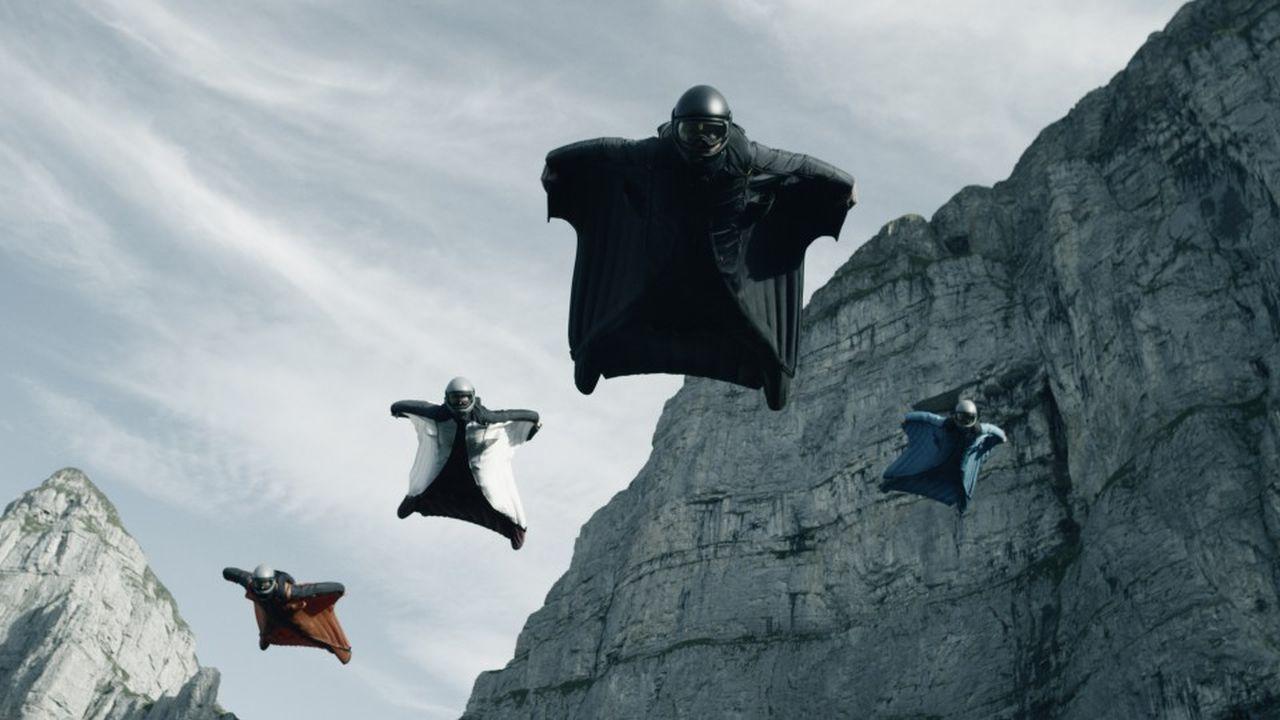 4 hombres en sus trajes sobrevuelan al lado de unas montañas altas