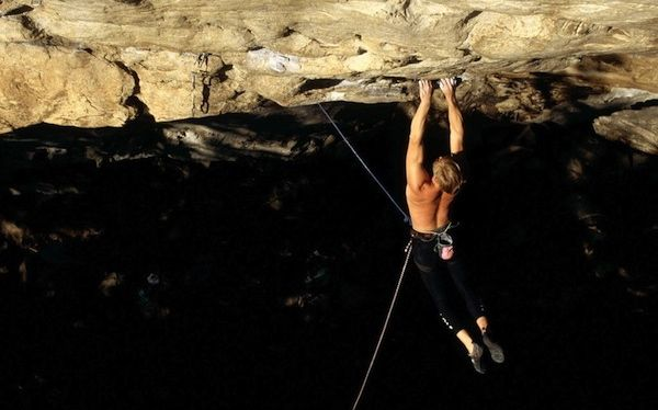 Un hombre cuelga peligrosamente de la pared rocosa de una montaña