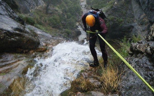Un hombre desciende por una cascada colgado de un cable de seguridad