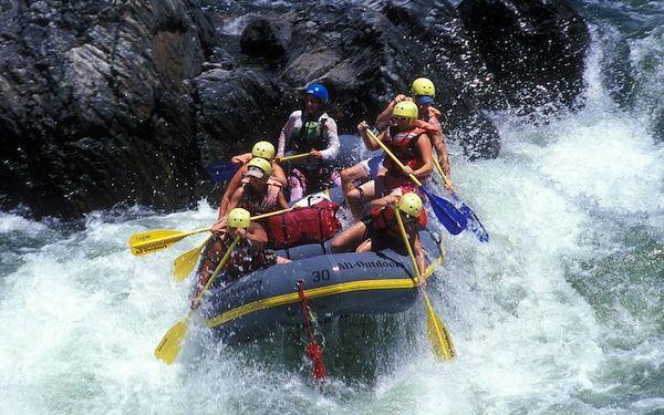 Seis personas en un bote luchan contra las aguas salvajes de un río