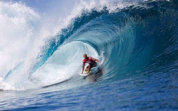 Un surfista montando sobre el estómago de una ola mediana