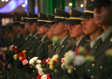 Vemos un grupo de militares en traje de ceremonia con claveles de colores en la mano
