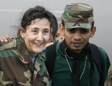 Vemos a una mujer con traje militar camuflado que es ayudada por  otro militar