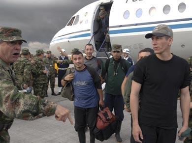 vemos un avión en una pista y varios hombres de uniforme camuflado y otros   de civil