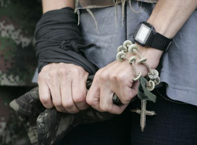 vemos las manos de una mujer que empuña una prenda militar