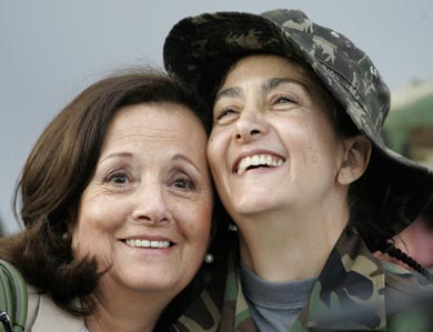 Dos mujeres sonríen abrazadas  se nota mucha alegria en sus rostros