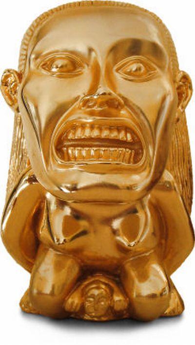 Vemos una mascara en color dorado   con ojos muy grandes y  muestra sus dientes
