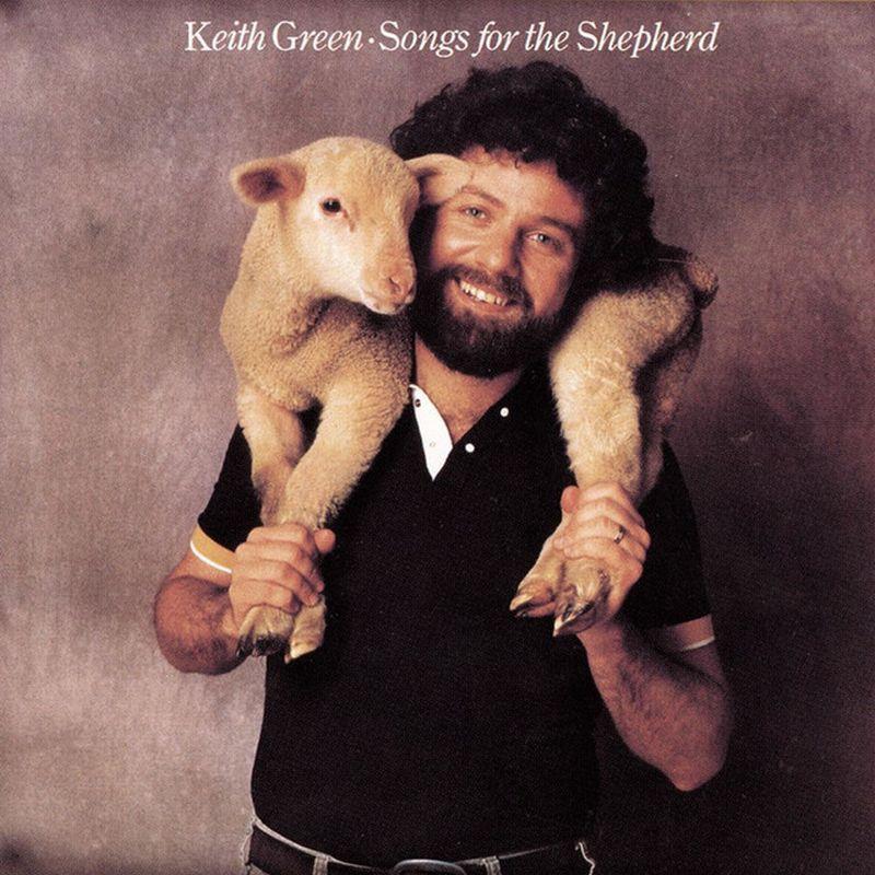 Un hombre cargando una oveja en su cuello  y riendo