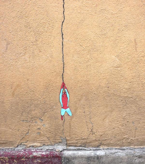 Tenemos una pared pintada en amarillo con una grieta que la recorre  de arriba hasta muy abajo y en la mitad pegado a la grieta aparece el hombre araña suspendido pareciendo que la grieta es una cuerda