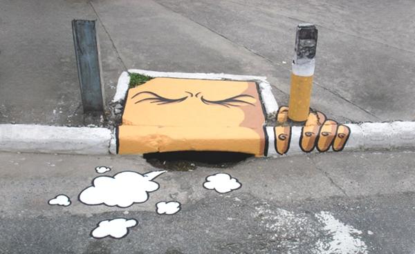 Vemos un anden y al borde de el aparece una pintura de una cara y unas manos que se sostienen al anden en color amarillo también simula tener un cigarrillo en las manos  y tose