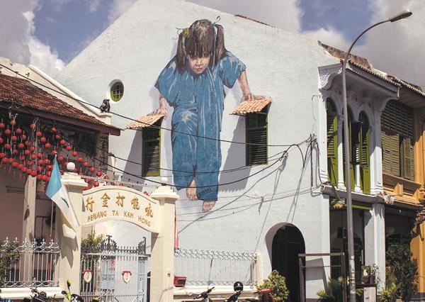 Vemos  unas lindas casas con rejas plantas y sobre una pared una niña pintada que trata de sostenerse sobre una cuerda de la luz