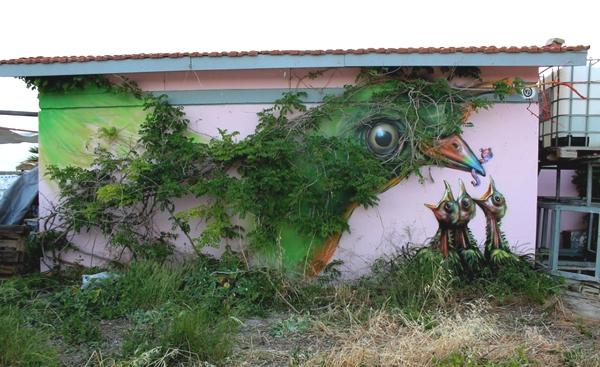 Tenemos una pared y sobre ela ha y una planta que esta organizada en forma de una gran ave y debajo hay un nido con unos pajaritos reales acabados de nacer que creen que ella es su madre