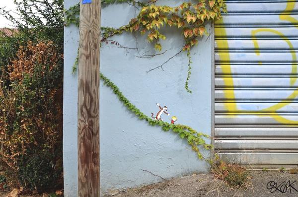Observamos una puerta de aluminio y enseguida una planta donde sale un pedazo largo donde encontramos a estos personajes de tiras comicas se ve tambien muchas plantas verdes