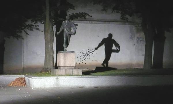 Vemos una estatua sobre un pedestal no muy alto al lado hay una pared donde la estatua hace sombra en ella se ven tambien tres arboles
