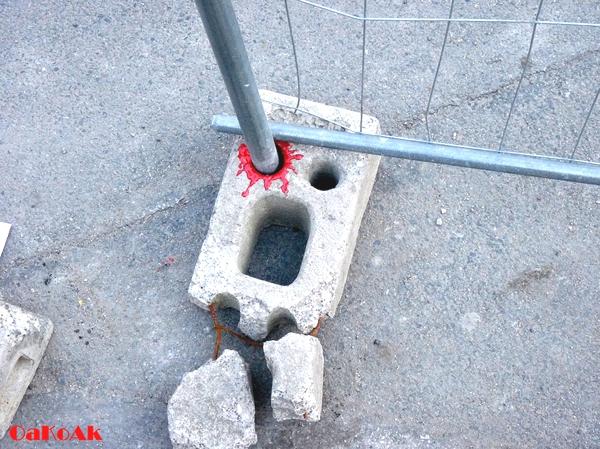 Tenemos una acera y hay un ladrillo que lo pasa un tubo tambien esta pintado de rojo  dando la impresión que perdio un ojo
