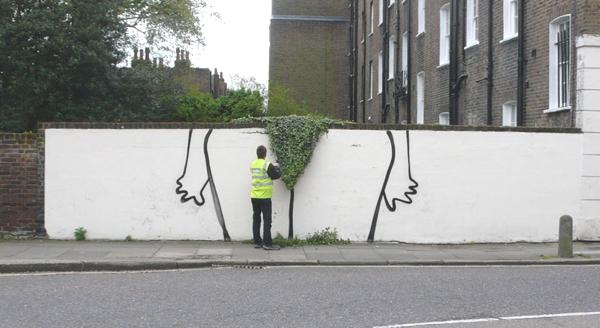 Observamos una figura fmenina sobre una pared blanca donde una parte de cesped crea la imagen de un pantalon interior de mujer