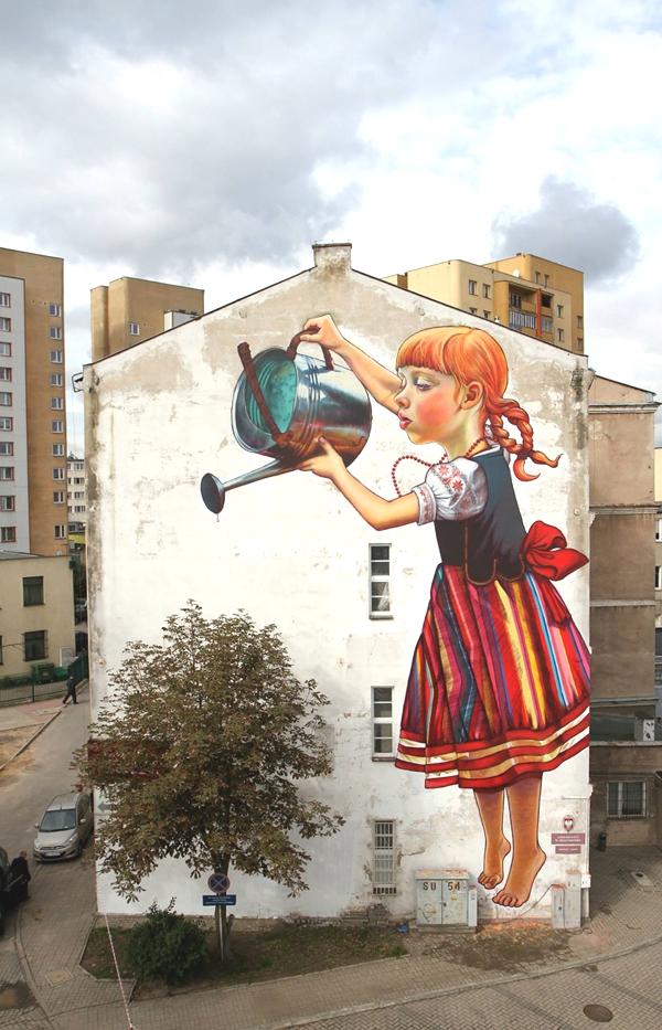 Vemos una pared donde una hermosa niña con regadera riega una planta que nace ahi mismo quedando integrada ala pintura