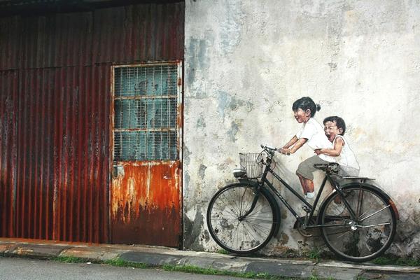 Observamos una vieja puerta metalica oxidada y al lado una pared de cemento donde hay una vieja bicicleta y pintaron sobre la pared unos niños que simulan estar montados sobre ella