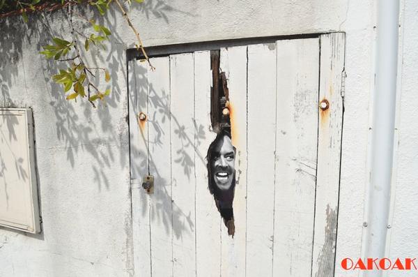 Hay una vieja puerta en madera blanca donde aparece el rostro de un hombrere joven sonriendo y da un aspecto que alguien estuviera alli