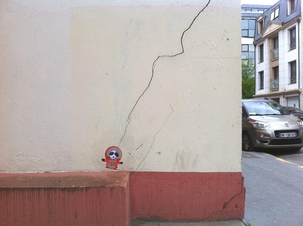Vemos una pared blanca con un zócalo rojo y una grieta que recorre toda la pared al final hay una muñeca que parece atada a una cuerda y es la grieta que hace las veces de cuerda