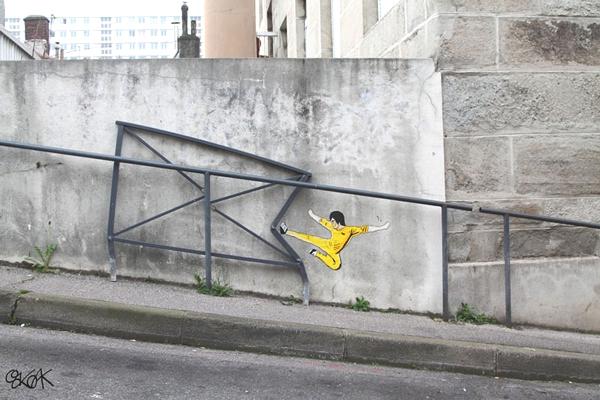 En la pared vemos a un hombre haciendo una figura de artes marciales sobre una pared de cemento donde hay unas cuadriculas de acero