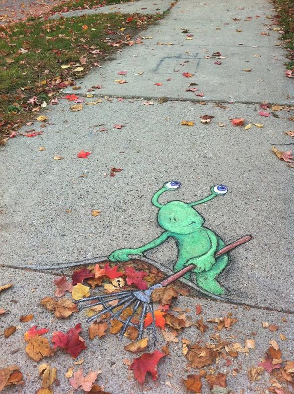 Observamos una calle con muchas hojas y flores secas caidas y un muñeco pintado que hace  trabajo con un rastrillo recoger todo lo que se ha caido de los arboles