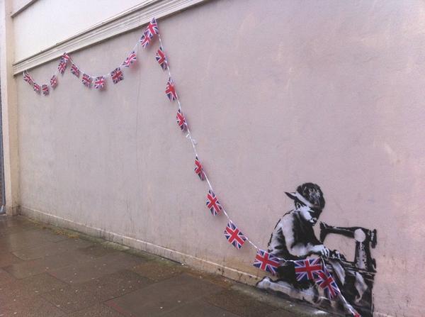 Vemos una pared de cemento donde se hallan unas banderas de Londres y al final de la pared un chico pintado con una maquina de coser que hace las banderas