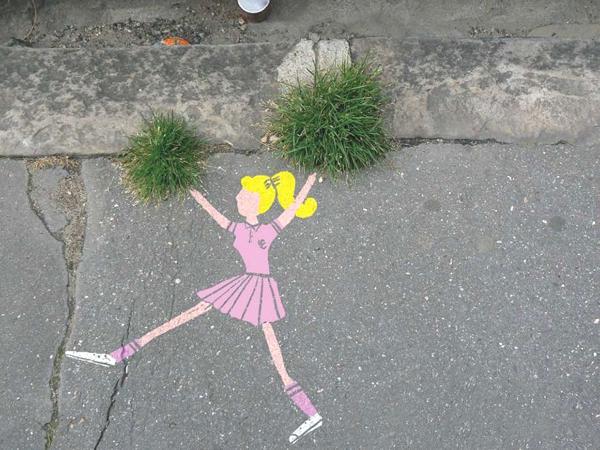 Vemos una pared de cemento donde observamos a una niña con traje rosado pintada ahí que sobresale un par de plantas que hace las veces de pompones