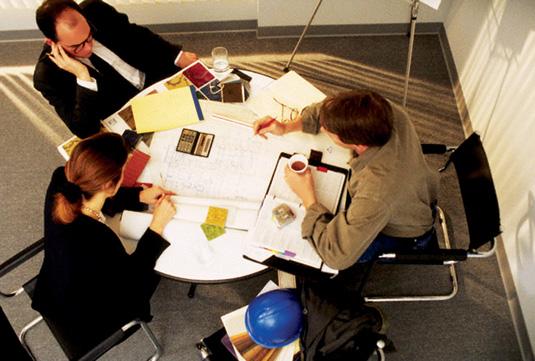 Vemos  a tres personas alrededor de una mesa trabajando en análisis de alguna  clase