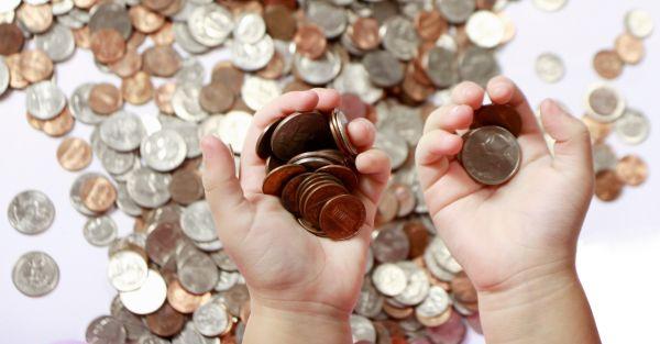 Unas manos sosteniendo montones de monedas y muchas mas al fondo