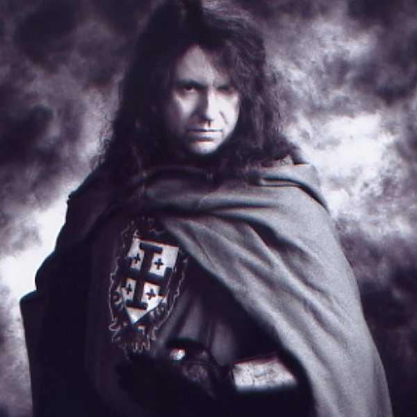 Un hombre joven con el pelo largo y una capa negra  con un escudo en su camiseta