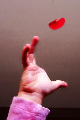 Vemos  una mano de bebe que quiere  un corazón de papel  que vuela