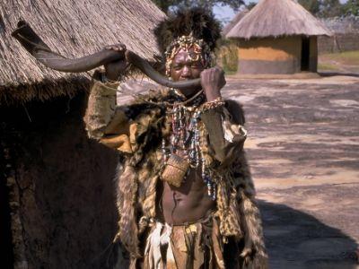 Tenemos aun hombre que toca un largo cuerno vestido con un traje echo como para un ritual