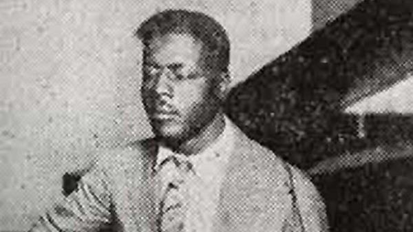 Un hombre moreno con traje y corbata sentado en una silla con los ojos cerrados