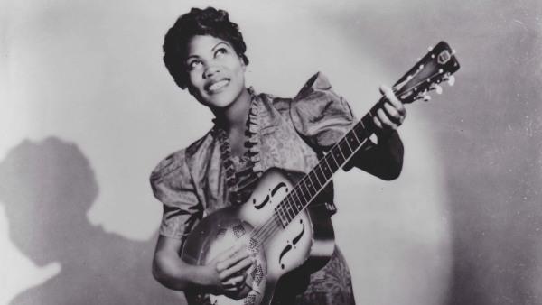 Una mujer tocando una guitarra de lado con una gran sonrisa mirando hacia arriba