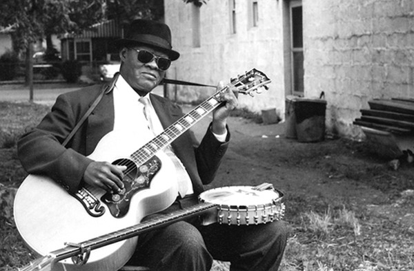 Un hombre con gafas negras tocando guitarra mientras en sus piernas tiene un banyo