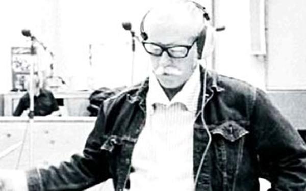 Un hombre de edad con gafas y auriculares mirando hacia abajo
