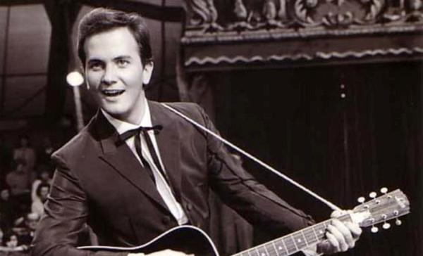 Un joven con una gran sonrisa tocando la guitarra en una presentación