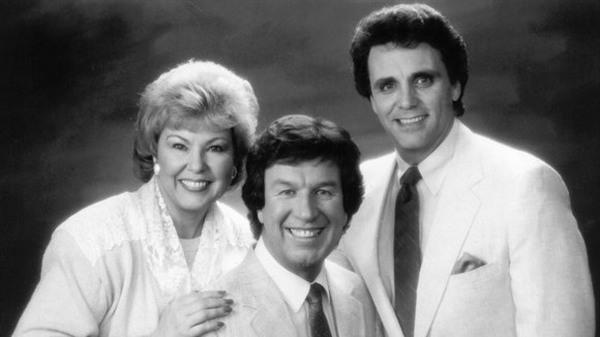 Dos hombres y una mujer de pelo corto, la mujer está al lado izquierdo  muy elegantes sonríen amablemente