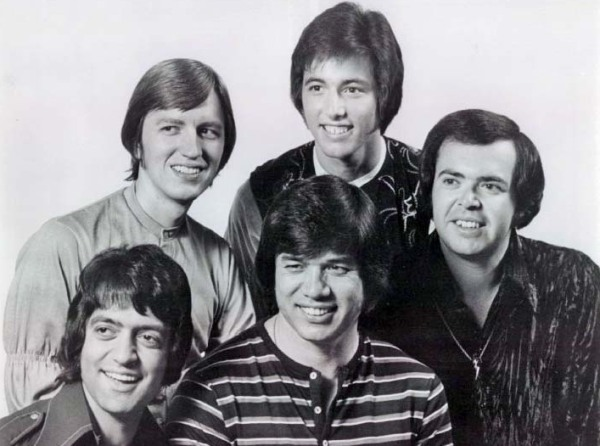 Un grupo de cinco jóvenes, todos con una sonrisa y corte de pelo de los sesenta