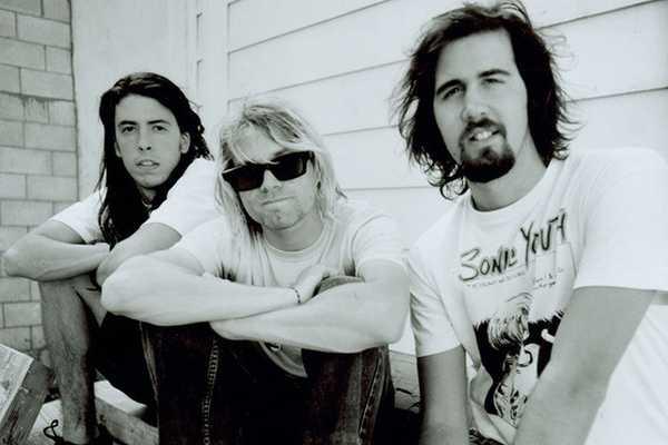 Vemos a tres jóvenes de pelo largo uno con pelo rubio y gafas mirando hacia a la cámara