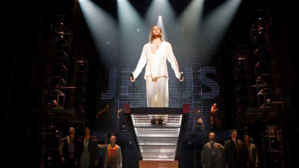 Tenemos un hombre rubio vestido de blanco donde un rayo de luz lo ilumina abajo vemos algunas personas